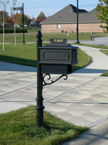 A small black iron mailbox on the side of the road.