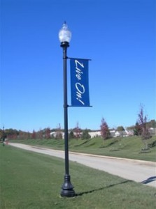 A tall streetlight in a suburban neighborhood, adorned with a decorative printed banner.